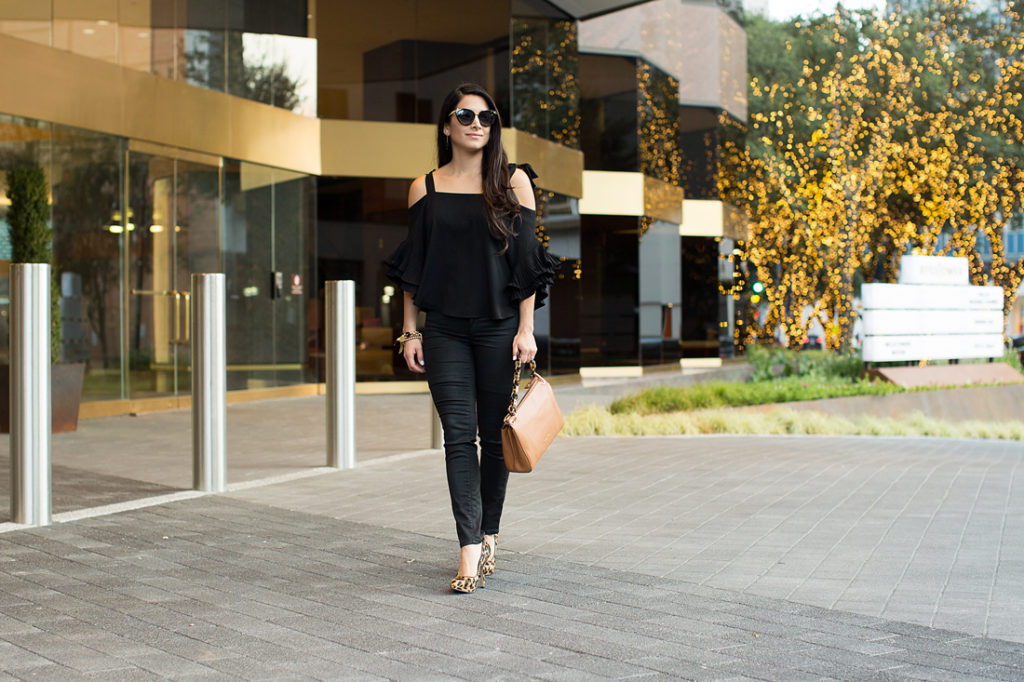 What can you wear with leopard print shoes?, all black outfit, black ruffle blouse, cold shoulder black blouse, ruffle black blouse, dressy black blouse, black skinny jeans, leopard pointed pumps, leopard shoes, black and gold sunglasses, black and gold cat eye sunglasses, black sunnies, gold and black accessories